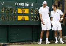 John Isner of the U.S. (L) and France's Nicolas Mahut pose for a photograph next to the scoreboard on court 18 after their record breaking match at the 2010 Wimbledon tennis championships in London, June 24, 2010.   REUTERS/Suzanne Plunkett