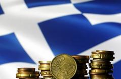 Euro coins are seen in front of a displayed Greece flag in this photo illustration taken in Zenica, Bosnia and Herzegovina, June 29, 2015. REUTERS/Dado Ruvic