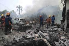 Firemen attempt to extinguish the fire surrounding the wreckage of an Indonesian military transport plane after it crashed in the North Sumatra city of Medan, Indonesia, June 30, 2015 in this photo taken by Antara Foto. An Indonesian military transport plane crashed into a hotel and houses in the northern Sumatra city of Medan on Tuesday, killing at least 30 people, an official said.The plane was on its way from an air force base in Medan to the remote Natuna islands and crashed a few minutes after takeoff. REUTERS/Irsan Mulyadi/Antara Foto ATTENTION EDITORS - THIS IMAGE HAS BEEN SUPPLIED BY A THIRD PARTY. IT IS DISTRIBUTED, EXACTLY AS RECEIVED BY REUTERS, AS A SERVICE TO CLIENTS. MANDATORY CREDIT. INDONESIA OUT. NO COMMERCIAL OR EDITORIAL SALES IN INDONESIA