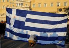 Un manifestante se arrodilla frente a la bandera de Grecia, durante una protesta anti-austeridad, en Atenas, Grecia, 29 de junio de 2015. Grecia intentó el martes un acercamiento de último minuto con sus acreedores internacionales en busca de ayuda, pero no fue suficiente para salvar al país de convertirse en la primer economía desarrollada en incumplir un préstamo con el Fondo Monetario Internacional. REUTERS/Yannis Behrakis