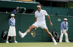 Roger Federer of Switzerland hits a shot through his legs during his match against Sam Querrey of the U.S.A. at the Wimbledon Tennis Championships in London, July 2, 2015.           REUTERS/Stefan Wermuth