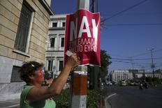 """Mulher cola cartaz em rua de Atenas com campanha pelo """"Sim"""" no referendo da Grécia. 03/07/2015 REUTERS/Alkis Konstantinidis"""