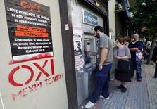 """Cartaz da campanha pelo """"Não"""" no referendo da Grécia ao lado de caixa eletrônico em Atenas. 03/07/2015 REUTERS/Jean-Paul Pelissier"""