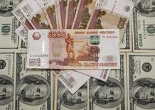 Рублевые и долларовые купюры в Сараево 9 марта 2015 года. Рубль подешевел к вечеру пятницы, выходного дня в США, благодаря которому были невысоки активность и объемы сделок на биржевых торгах, из-за нежелания рисковать в ожидании свежего рейтинга России от агентства Fitch и итогов греческого референдума 5 июля. REUTERS/Dado Ruvic