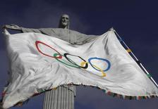 """The Olympic Flag flies in front of """"Christ the Redeemer"""" statue during a blessing ceremony in Rio de Janeiro August 19, 2012.  REUTERS/Ricardo Moraes"""