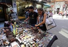 Personas mirando productos relacionados a la marihuana en una calle comercial en el centro de Montevideo. 10 de marzo de 2014. Los precios minoristas avanzaron en Uruguay un 0,45 por ciento en junio, en línea con las expectativas de los analistas, dijo el viernes el Gobierno. REUTERS/Andres Stapff