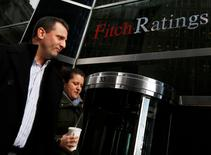 People walk past the headquarters of Fitch Ratings in New York, February 6, 2013. REUTERS/Brendan McDermid (UNITED STATES - Tags: BUSINESS) - RTR3DFL3