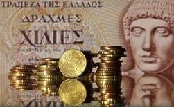 Монеты валюты евро на фоне купюры прежней греческой валюты драхмы в Зенице 30 июня 2015 года. Отрицательный результат референдума в Греции усложнил ее дальнейшие переговоры с кредиторами, но целью по-прежнему  является удержание страны в зоне евро, сказал председатель Еврогруппы Йерун Дейсселблум в понедельник. REUTERS/Dado Ruvic