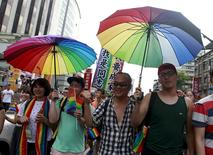 Participants hold rainbow umbrellas during a rally to demanding the Taiwanese government to legalize same-sex marriage in front of the ruling Nationalist Kuomintang Party headquarters in Taipei, Taiwan, July 11, 2015. REUTERS/Pichi Chuang