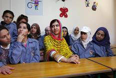 Nobel Peace Prize laureate Malala Yousafzai (C) sits with girls inside a classroom at a school for Syrian refugee girls, built by the NGO Kayany Foundation, in Lebanon's Bekaa Valley July 12, 2015. REUTERS/Jamal Saidi