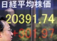 Мужчина проходит мимо экрана брокерской конторы в Токио, показывающего динамику индекса Nikkei average. 14 июля 2015 года. Азиатские фондовые рынки, кроме Японии, снизились во вторник вслед за Китаем, корректируясь после бурного роста в предыдущие несколько дней. REUTERS/Toru Hanai