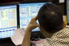 Инвестор в брокерской конторе в Гонконге. 8 июля 2015 года. Азиатские фондовые рынки выросли в четверг благодаря комментариям председателя ФРС Джанет Йеллен, предсказавшей продолжение роста американской экономики. REUTERS/Tyrone Siu