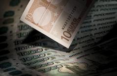 Банкноты российского рубля и евро. 17 февраля 2014 года. Рубль незначительно подорожал при открытии пятничной биржевой сессии, отражая умеренный рост котировок нефти при нейтральном в целом внешнем фоне. REUTERS/Maxim Shemetov