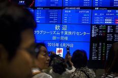 Visitantes miran una pantalla que muestra los índices de mercado, en la Bolsa de Tokio, 29 de junio de 2015. Las bolsas de Asia avanzaban el viernes luego de que las acciones chinas extendieron su recuperación, y el dólar mantenía sus ganancias frente al euro y el yen luego de que unos indicadores económicos reforzaron las expectativas de un alza en las tasas de interés en Estados Unidos a finales de este año. REUTERS/Thomas Peter