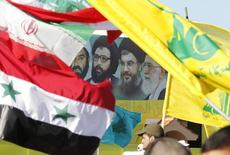 A poster of (R-L) Iran's supreme leader Ayatollah Ali Khamenei, Hezbollah Secretary-General Sayyed Hassan Nasrallah, former Hezbollah Secretary-General Sayyed Abbas al-Musawi and Lebanese resistance leader and cleric Sheikh Ragheb Harb, is seen in between Iranian, Syrian, Lebanese and Hezbollah flags during Resistance and Liberation Day celebrations in Bint Jbeil May 25, 2014. The event commemorates the 14th anniversary of Israel's withdrawal from southern Lebanon.  REUTERS/Ali Hashisho (LEBANON - Tags: POLITICS ANNIVERSARY)