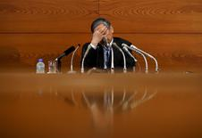 Bank of Japan (BOJ) Governor Haruhiko Kuroda touches his face during a news conference at the BOJ headquarters in Tokyo, July 15, 2015. REUTERS/Yuya Shino