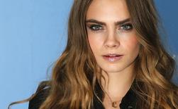 """Cast member Cara Delevingne poses for photos at a photo call promoting her film """"Paper Towns"""" at Claridges in London, Britain June 18, 2015.   REUTERS/Suzanne Plunkett"""