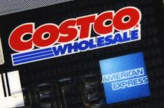Corporate logos are seen on the rear of a Costco membership card/American Express credit card in this photo illustration taken in Toronto, Ontario February 12, 2015. Квартальная прибыль эмитента кредитных карт American Express Co <AXP.N> оказалась выше прогнозов благодаря экономии средств после сокращения штата.  REUTERS/Hyungwon Kang
