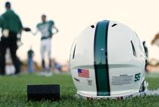 A football helmet's health warning sticker is pictured between a U.S. flag and the number 55, in memory of former student and NFL player Junior Seau, as the Oceanside Pirates high school football team prepares for their Friday night game in Oceanside, California September 14, 2012. Picture taken September 14, 2012.   REUTERS/Mike Blake