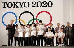 Yoshiro Mori (2nd R), Japan's former Prime Minister and president of the Tokyo 2020, and Tokyo Governor Yoichi Masuzoe (5th R) and athletes pose for a photograph during an unveiling event for the Tokyo 2020 Olympic and Paralympic games emblems at Tokyo Metropolitan Government Building in Tokyo July 24, 2015. REUTERS/Issei Kato