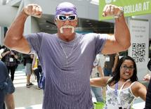 """Wrestler Hulk Hogan poses for a photo as a fan also poses as he walks in the Los Angeles Convention Center while on site to promote Majesco Entertainment's """"Hulk Hogan's Main Event"""" video game on Kinect for Xbox 360 during the Electronic Entertainment Expo or E3 in Los Angeles June 7, 2011. REUTERS/Danny Moloshok"""