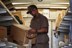 Foto de archivo de un trabajador de UPS controlando una caja de Amazon para ser despachada en Nueva York. Jul 24, 2015. El entusiasmo de los inversores por Amazon.com Inc es bastante consistente: el precio de la acción tiende a subir, aun cuando la empresa no tenga la misma estabilidad para generar ganancias. REUTERS/Eduardo Munoz