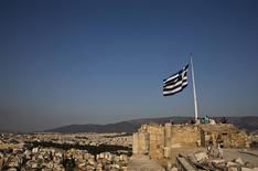 La bandera de Grecia ondea mientras los turistas visitan la Acrópolis, en Atenas, Grecia, 26 de julio de 2015. Los jefes de la misión de la Unión Europea y el Fondo Monetario Internacional llegarán a Atenas al final de la semana para iniciar las conversaciones que sellen un tercer rescate, después de un retraso debido a cuestiones de organización, dijeron el lunes fuentes cercanas a las negociaciones. REUTERS/Ronen Zvulun