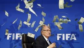 British comedian known as Lee Nelson (unseen) throws banknotes at FIFA President Sepp Blatter as he arrives for a news conference after the Extraordinary FIFA Executive Committee Meeting at the FIFA headquarters in Zurich, Switzerland July 20, 2015. REUTERS/Arnd Wiegmann