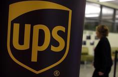 Una mujer camina junto a un cartel con el logo de UPS, en una feria de empleos en Chicago, Illinois, 18 de octubre de 2014. La compañía estadounidense de transporte de encomiendas United Parcel Service Inc reportó el martes un aumento de sus utilidades netas trimestrales, gracias a una mejoría en sus márgenes que compensó una leve caída en los ingresos. REUTERS/Jim Young
