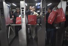 Personas entrando con bolsas en una estación de metro en Nueva York, 28 de noviembre de 2014. La confianza del consumidor estadounidense registró su mayor caída en cuatro años en julio debido a un panorama laboral menos alentador, mientras que la valorización de las casas en grandes ciudades se estancó en mayo, un hecho que sugiere una pausa en la demanda por viviendas. REUTERS/Carlo Allegri