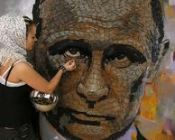 Украинская художница Дарья Марченко у сделанного ею из гильз, собранных на востоке Украины, портрета Владимира Путина. Киев, 23 июля 2015 года. Владимир Путин в разговоре с позвонившим премьером Нидерландов Марком Рютте вновь высказался против трибунала для расследования падения боинга на Украине, сообщил Кремль в среду, в преддверии обсуждения вопроса в Совбезе ООН, где у Москвы есть право вето. REUTERS/Gleb Garanich