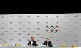 President of the International Olympic Committee (IOC) Thomas Bach speaks next to IOC Director of Communications Mark Adams at a news conference following the IOC executive board meeting in Kuala Lumpur, Malaysia, July 29, 2015. REUTERS/Olivia Harris