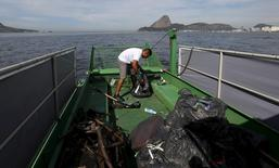 A worker inside a garbage-collecting boat collects the remains of garbage from the Guanabara Bay in Rio de Janeiro, Brazil, July 1, 2015. The International Olympic Comittee (IOC) is still concerned about the water pollution in Rio de Janeiro barely one year before it hosts the 2016 Olympic Games, its president Thomas Bach said earlier in June. Rio de Janeiro had originally pledged to reduce pollution in the notoriously fetid Guanabara Bay by 80 percent but officials confirmed in March that the target will not be reached. Instead, they are now concentrating only on parts of the bay where sailing competitions will take place although they have insisted that these areas will be safe. The garbage-collecting boat resumed cleaning on Wednesday after stopping four months ago, 45 days before a sailing event test for the Olympics. REUTERS/Sergio Moraes