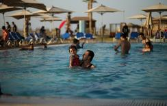 A Palestinian man holding his daughter swims in a pool as they enjoy the warm weather with their family at the Blue Beach Resort in Gaza July 30, 2015. REUTERS/Mohammed Salem