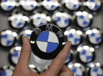 An employee holds a BMW logo on the production line of the BMW C evolution electric maxi-scooter at the BMW Berlin motorcycle plant February 23, 2015.  REUTERS/Fabrizio Bensch