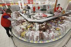 Работники мясного отдела магазина Ашан раскладывают продукты. Москва, 28 ноября 2014 года. Потребительские цены в РФ выросли в июле 2015 года на 0,8 процента к предыдущему месяцу и на 15,6 процента - к аналогичному периоду предыдущего года, сообщил Росстат. REUTERS/Sergei Karpukhin