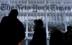 People stand across the street from the New York Times head office in New York, in this February 7, 2013, file photo.   REUTERS/Carlo Allegri/Files