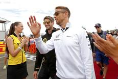 McLaren Formula One driver Jenson Button of Britain (R) and Lotus Formula One driver Romain Grosjean of France arrive for the drivers parade before the Hungarian F1 Grand Prix at the Hungaroring circuit, near Budapest, Hungary July 26, 2015. REUTERS/Laszlo Balogh