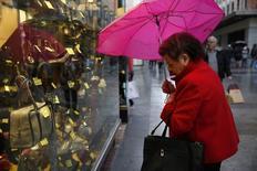Женщина рассматривает товары за витриной магазина в Мадриде. 30 января 2015 года. Инфляционное давление в еврозоне ослабело, но все же сохраняет тенденцию к росту, согласно индикатору, разработанному для прогнозирования циклических тенденций. REUTERS/Susana Vera