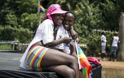 A lesbian couple laughs during the third annual gay pride celebrations by members of the lesbian, gay, bisexual and transgender (LGBT) community in Entebbe, southwest of Uganda's capital Kampala, August 8, 2015. REUTERS/Edward Echwalu