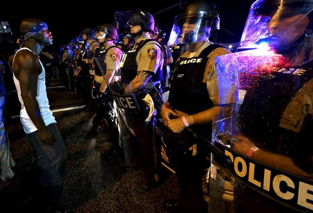 A protester yells at a police line shortly before shots were fired in a police-officer involved shooting in Ferguson, Missouri August 9, 2015.  REUTERS/Rick Wilking