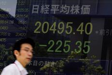 Un hombre camina junto a un tablero que muestra el índice Nikkei en Tokio, 12 de agosto de 2015. El índice Nikkei de la bolsa de Tokio subió el jueves luego que el banco central de China calmó los mercados diciendo que no hay base para una depreciación adicional del yuan. REUTERS/Thomas Peter