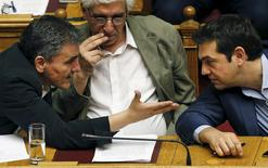 Greek Prime Minister Alexis Tsipras (R) listens to Finance Minister Euclid Tsakalotos as Justice Minister Nikos Paraskevopoulos (C) looks on during a parliamentary session in Athens, Greece July 23, 2015. REUTERS/Yiannis Kourtoglou