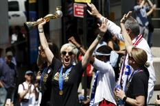 U.S. women's soccer player Megan Rapinoe (C) holds the Wold Cup trophy as she rides a float with team mate Carli Lloyd (L) and New York Mayor Bill de Blasio (back R) during the ticker tape parade up Broadway in lower Manhattan to celebrate their World Cup final win over Japan in New York, July 10, 2015.  REUTERS/Mike Segar -
