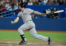 Aug 14, 2015; Toronto, Ontario, CAN; New York Yankees third baseman Chase Headley (12) hits a single to score a run against Toronto Blue Jays in the eighth inning at Rogers Centre. The Yankees won 4-3. Mandatory Credit: Dan Hamilton-USA TODAY Sports