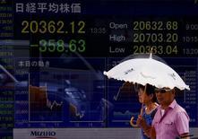 Personas caminan junto a un tablero electrónico que muestra el índice Nikkei de Japón, en Tokio, 12 de agosto de 2015. El índice Nikkei de la Bolsa de Tokio retrocedió 0,3 por ciento el martes, golpeado por la debilidad de los mercados de futuros y de otras bolsas de Asia ante preocupaciones de los inversores sobre la desaceleración económica de China. REUTERS/Thomas Peter