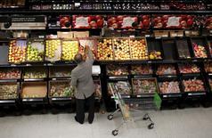 Un hombre escoge manzanas en una tienda Asda en el noroeste de Londres, 18 de agosto de 2015.  August 18, 2015. La inflación británica se aceleró en julio, según mostraron el martes datos oficiales, impulsada por unos descuentos en la ropa inferiores a los del año anterior, mientras que la inflación subyacente alcanzó un máximo de cinco meses. REUTERS/Suzanne Plunkett