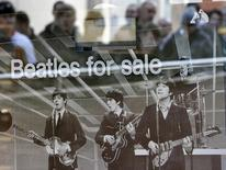 "Shoppers are reflected in a window as they queue at a HMV store for the launch of the game ""The Beatles: Rock Band"" in Liverpool, northern England, September 9, 2009.   REUTERS/Darren Staples"