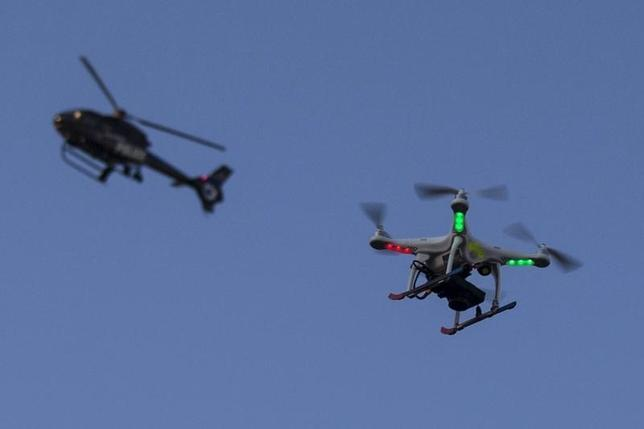 A police helicopter flies past a UAV drone Quadcopter which was flying over a post-march street celebration in west Baltimore, Maryland May 2, 2015. REUTERS/Adrees Latif
