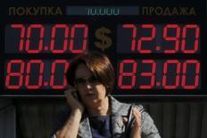 Женщина говорит по телефону, проходя мимо табло с курсами валют в Москве 24 августа 2015 года. Рубль за счет продаж экспортной выручки приостановил падение в середине понедельника после достижения очередного многомесячного дна в ответ на обвал нефти Brent к уровням марта 2009 года, а сырьевых и развивающихся валют - на многолетние минимумы из-за опасений замедления экономического роста в Китае. REUTERS/Maxim Shemetov